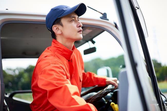 つなぎを着てトラックに乗る男性