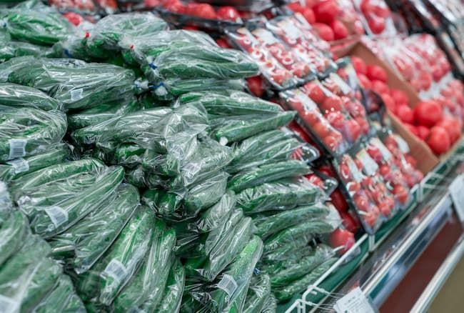 トマトときゅうりが山積みされているスーパーの野菜売り場