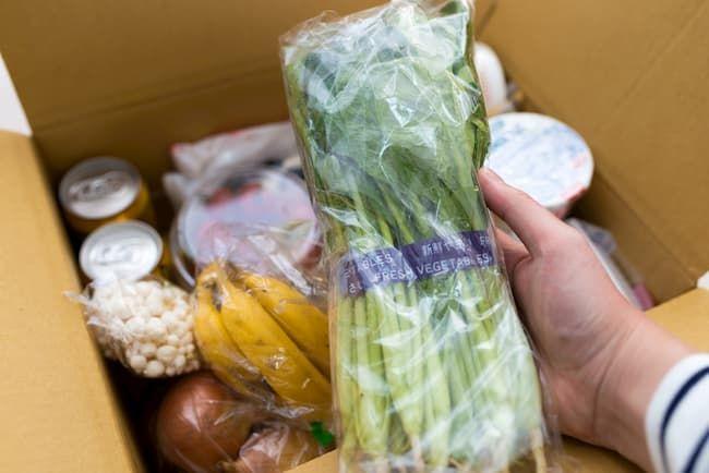 野菜の通販 ダンボールから小松菜を取り出す消費者